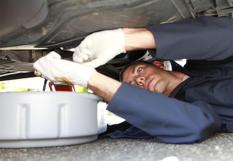 Man Changing Car Oil Laying Under Vehicle.